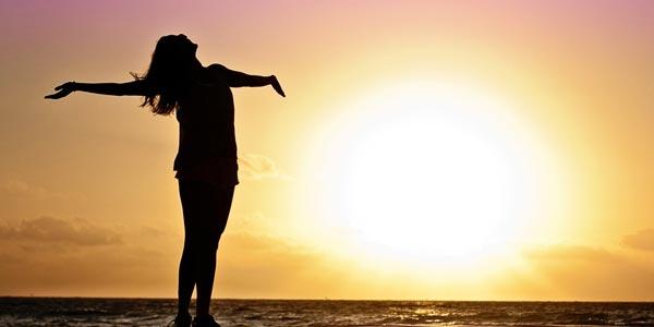 Frau steht am Strand und reckt sich zur Sonne