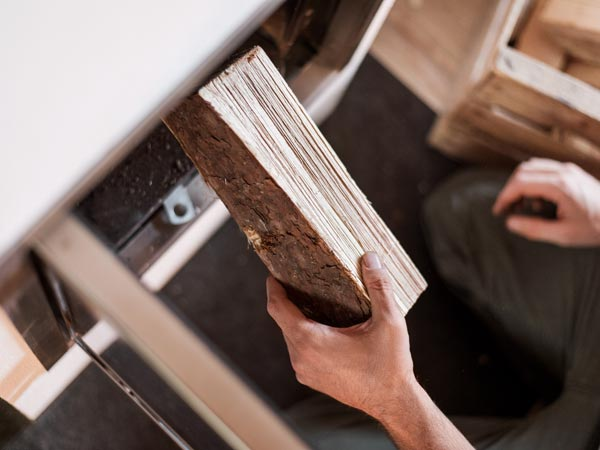 Holzscheit wird eingelegt