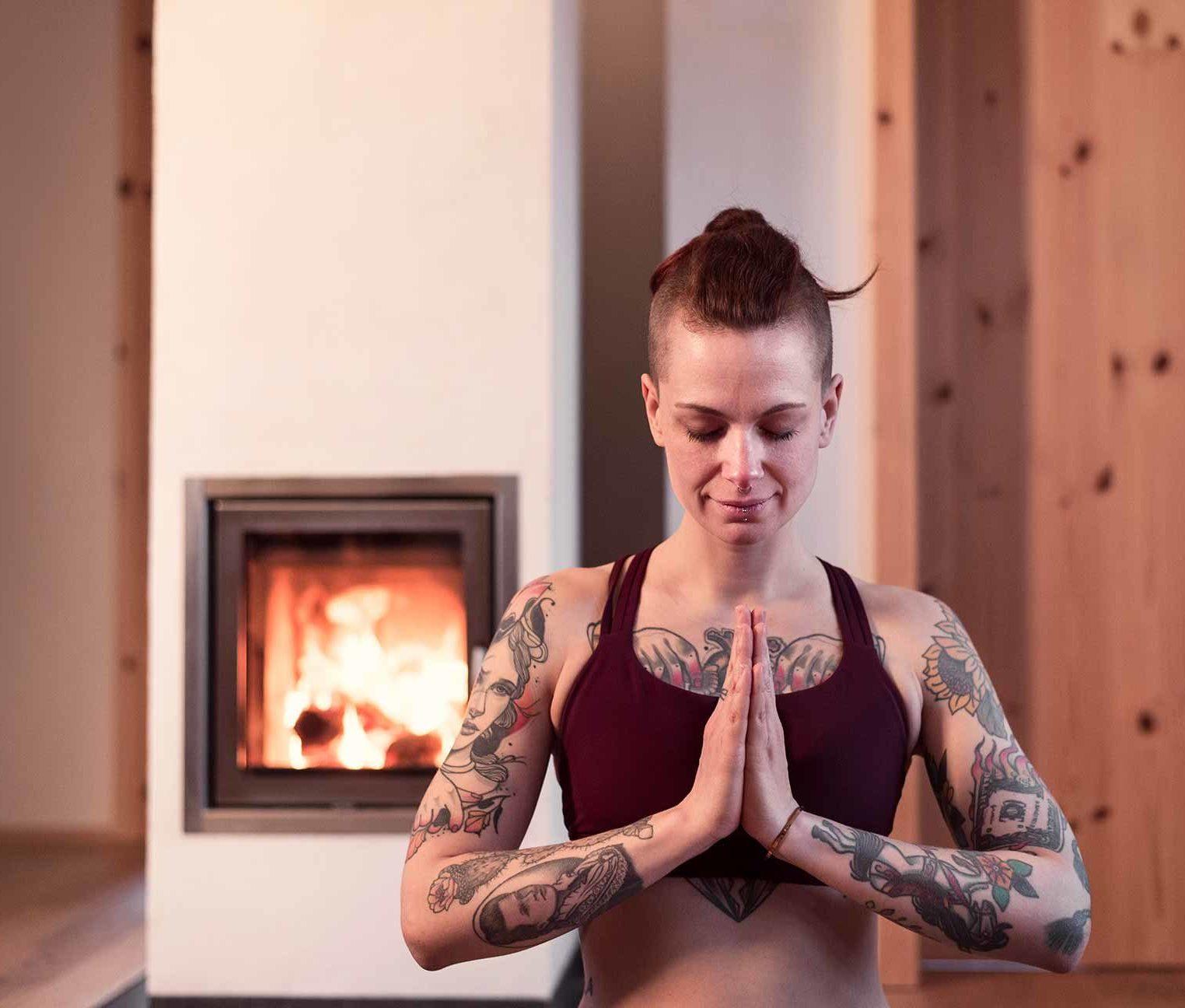 Frau meditiert vor Ofen